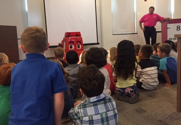 Kindergarteners watch Freddy the talking fire truck.